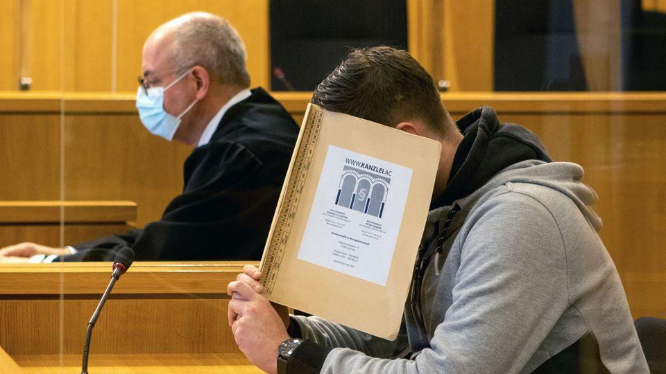 Hinter einer beigen Mappe verbirgt ein junger weißer Mann sein Gesicht. Er hat einen gegelten braunen Seitenscheitel