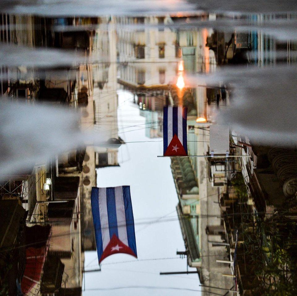 Havanna, Kuba. Nur wenn man genau hinschaut, erkennt man, dass die Flaggen nur ein Spiegelbild in einer Pfütze sind. DieHauptstadt– mit vollständigem Namen Villa de San Cristóbal de la Habana –ist nicht nur das politischeZentrum des Landes, sie ist auch bei Touristen sehr beliebt. Knapp die Hälfte aller Besucher Kubas reist nach Havanna,um Urlaub zu machen.