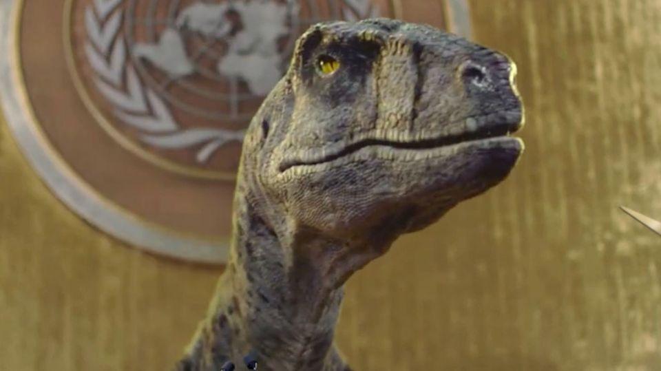 Ein Dinosaurier steht vor dem Rednerpult des UNO-Parlamentes.