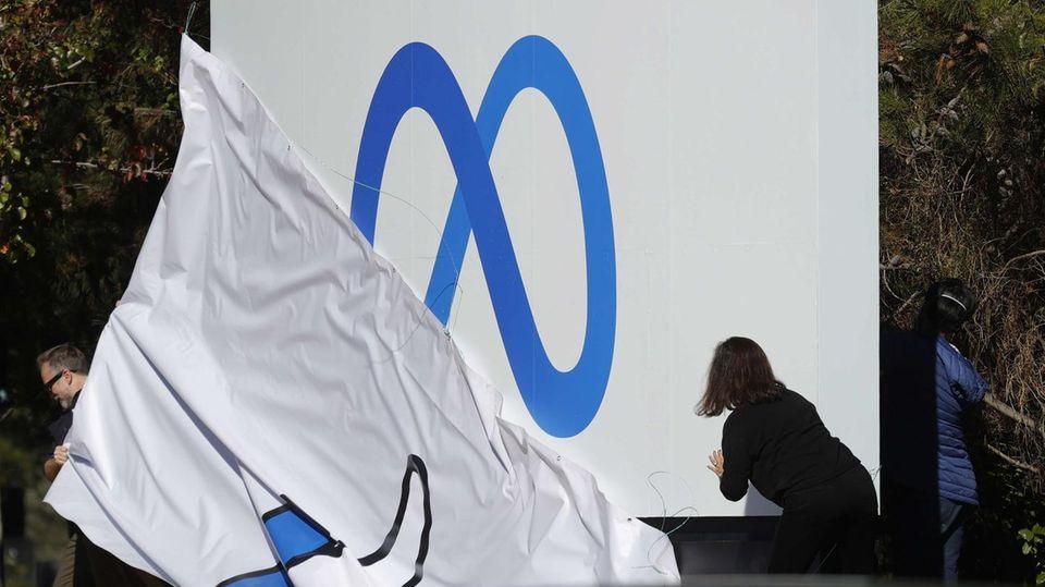 Eine Mitarbeiterin enthüllt das neue Logogegenüber des Facebook-Hauptquartier