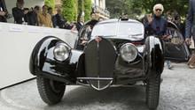"""Der Star des diesjährigen Concorso d'Eleganza Villa D'Este war kaum zu sehen. Eine Menschentraube bildete sich regelmäßig um den schwarzen Bugatti 57SC Atlantic aus dem Jahr 1938. Das atemberaubende Gefährt, von dem nur vier Stück gebaut wurden, ist rund 27 Millionen Euro wert. Nicht minder berühmt ist der Besitzer der automobilen Preziose, der weltbekannte Mode-Zar Ralph Lauren. Der amerikanische Multimilliardär ließ es sich nicht nehmen, sein Schmuckstück selbst zu lenken und heimste prompt den ersten Preis ein, den """"Coppa d'Oro Villa d'Este"""".  Doch das Fahrzeug, das mit seinem genieteten Falz, der sich längs über das Fahrzeug entlangzieht, ein bisschen so aussieht wie die Nautilus des Kapitän Nemo, war nicht das einzige Highlight auf dem edlen Automobil-Treffen an dem Ost-Ufer des pittoresken Comer Sees. Mit der Startnummer 46 präsentierte der Engländer Edward Stratton stolz seinen orangefarbenen Aston Martin DBS von 1970. Das wunderschöne Coupé ist für sich schon ein Klassiker doch dieses Auto ist etwas ganz Besonderes: Es ist das Original-Fahrzeug aus der legendären Fernsehserie """"Die Zwei"""" (""""The Persuaders"""") in der Roger Moore und Tony Curtis alias Lord Brett Sinclair und Danny Wilde mit lockeren Sprüchen und harten Fäusten auf Verbrecherjagd gingen. Beide Stars haben es sich nicht nehmen lassen, auf der Innenseite des Kofferraum-Deckels zu unterschreiben.  So ein Auto zu besitzen ist eine Sache, es in Schuss zu halten, eine andere. Der DBS ist in makelloser Verfassung. Deswegen muss der freundliche Brite mit dem Strohhut auch jährlich nur 2000 englische Pfund (2339 Euro) in die Erhaltung seines Schmuckstückes investieren. Ganz im Gegensatz zum Vorbesitzer, der das Auto hütete, wie seinen Augapfel, fährt Stratton pro Jahr 3000 bis 4000 Kilometer. """"Ich stelle das Auto nur bei den besten Shows aus"""", sagt Edward Stratton. Da liegt er genau richtig: Das Jahrestreffen im Norden Italiens ist die exklusivste Oldtimer-Zusammenkunft der Welt."""