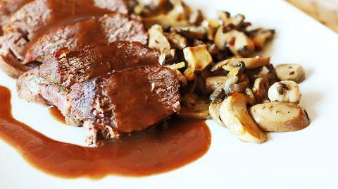 Ein Teller mit Fleisch, Pilzragout und Bratensoße