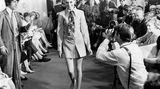 Es ist eher ungewöhnlich, dass ein Kleidungsstück nach dem Model benannt wird, das es präsentiert. In diesem Fall ist es anders: Bis heute ist der Schnitt als Twiggy-Kleid bekannt. Das Model präsentiert es mit einnem bunten Schlips.