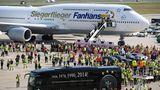 """Mit einer besonderen Maschine landete die Mannschaft von Jogi Löw nach dem erfolgreichen Ende der Fußballweltmeisterschaft in Brasilien zur Jubelparade in Berlin. Für den Sonderflug LH2014 hatte die Lufthansa eine Boeing 747-8 mit dem """"Siegerflieger""""- Schriftzug geschmückt."""
