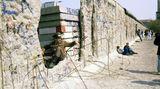 Die Mauer war schon gefallen, doch die DDR bestand noch: ein Grenzsoldat inmitten der Mauerreste