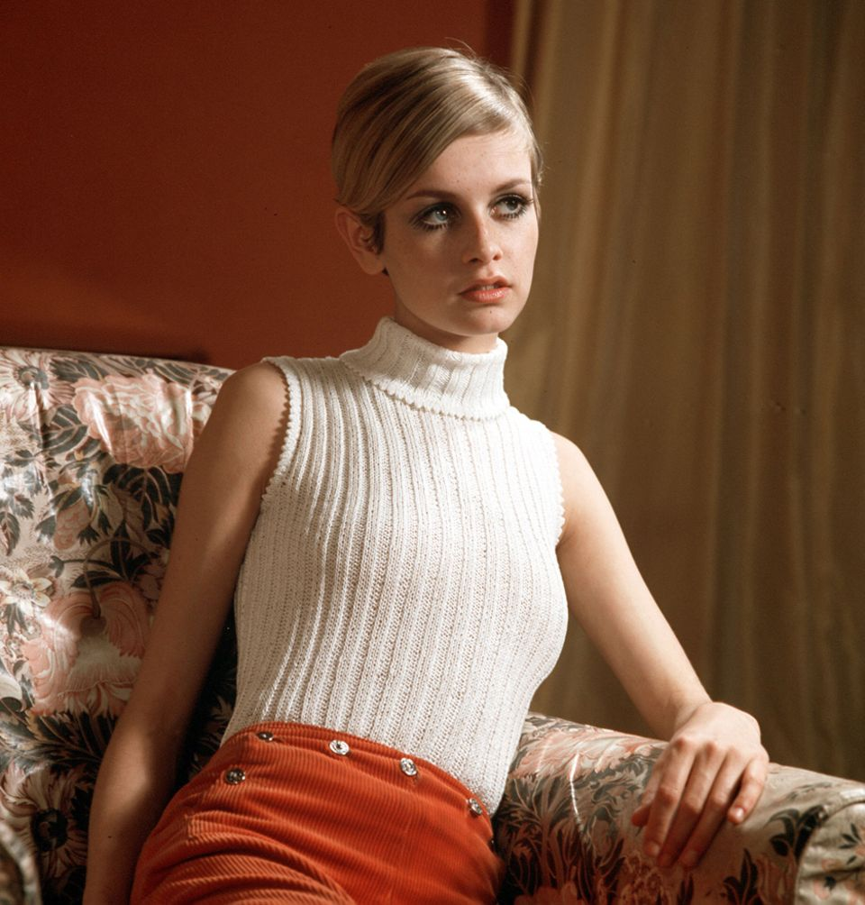 Dieses Foto aus dem Jahr 1967 zeigt Twiggy auf dem Sofa sitzend in einem modischen weißen Strickpullover.
