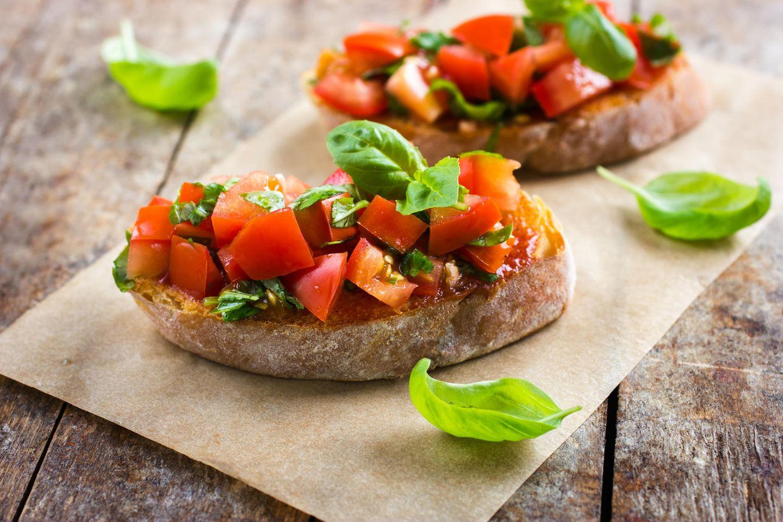 Bruschetta  Bruschetta kommt vom italienischen Wort bruciare für verbrennen. Gemeint ist das römische Brot, das leicht angebrannt ist. Das ist sehr typisch für die römische Bruschetta. Das angeröstete Brot wird mit Knoblauch eingerieben und mit Tomaten und Olivenöl belegt. Hier im Bild sieht man eine Variation mit getrockneten Tomaten. Hier geht's zum Rezept.