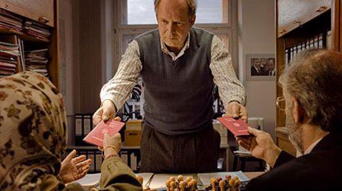 """Der Einwanderungsbeamte (Axel Milberg) überreicht zwei eingewanderten Neubürgern ihre deutschen Pässe - und ermahnt sie, immer schön sonntags den """"Tatort"""" zu gucken"""