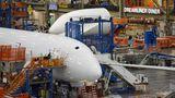 Noch sind die Cockpitscheiben hinter weißer Kunststofffolie verborgen: Nicht aus glänzenden Aluminium wird der Rumpf zusammengenietet, sondern aus vorgefertigten Baugruppen. Im Hintergrund ist eine Kantine für die Boeing-Mitarbeiter zu sehen: der Dreamliner Diner.