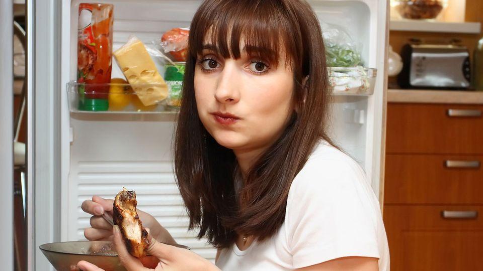 Teenager isst vorm Kühlschrank