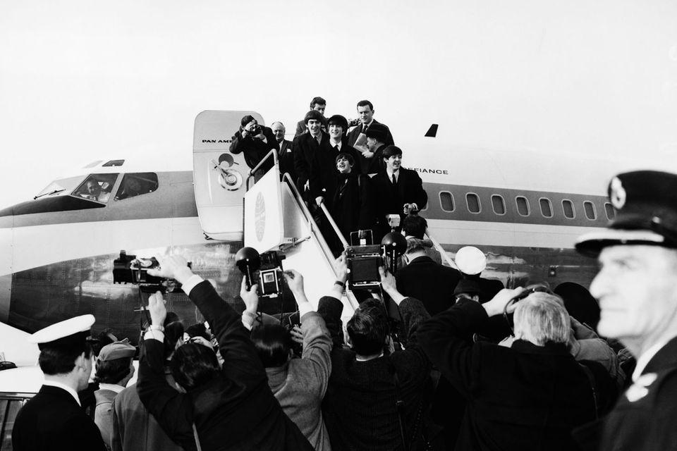 """Als sie in London das Flugzeug bestiegen, waren sie nur eine sehr erfolgreiche britische Band. Doch als die Beatles am 7. Februar 1964 das Flugzeug verließen, wurden sie empfangen wie Weltstars: 5000 Fans und 200 Journalisten bereiteten den Beatles auf dem Rollfeld des New Yorker Flughafens einen überwältigenden Empfang.  Wenige Wochen zuvor hatte ihre Single """"I Want to Hold Your Hand"""" bereits in den USA die Chartspitze erobert. Ein erster Erfolg, doch erst mit ihrer Ankunft vor genau 50 Jahren wurden die Beatles auch jenseits des Kanals zur wohl größten Popband, die es je gegeben hat.Im April 1964 besetzten sie dort sogar die ersten fünf Plätze der Single-Charts. Auch das hat es davor und danach nicht mehr gegeben."""