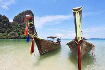 Farbenfroh verzierte Longtail-Boote liegen am Strand von Phuket