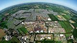 """Das Festival-Gelände und der Campground aus der Luft. Die Äcker sind übersät mit Zeltplätzen, Wagenburgen, Imbissbuden und zahlreichen Bühnen; die Wege zwischen den Campground-Arealen sind benannt nach berühmten Bands (""""AC/DC Street"""", """"Nightwish Boulevard"""", """"Metallica Avenue"""")."""