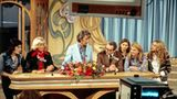 """""""Am laufenden Band"""" war in den 70er Jahren die größte Show im deutschen Fernsehen - vergleichbar mit """"Wetten, dass ..?"""" in den 80ern. Und Rudi Carrell war der kongeniale Moderator und Showman: Er war schlagfertig, sang und trat in Sketchen auf. Und er holte den großen Muhammad Ali in die Sendung. Fünf Jahre lang, von 1974 bis 1979, gelang hier das seltene Kunststück, Publikum wie Kritiker gleichermaßen zu versöhnen. 2006 versuchte sich Florian Silbereisen an einem Remake, 2014 moderierte Jörg Pilawa eine einmalige Neuauflage anlässlich des 80. Geburtstages von Rudi Carrell."""