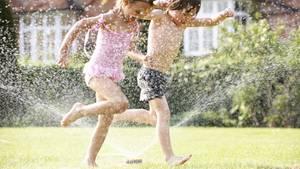 Mit einem Rasensprenger wird aus dem heimischen Garten ein Wasserparadies für Kinder