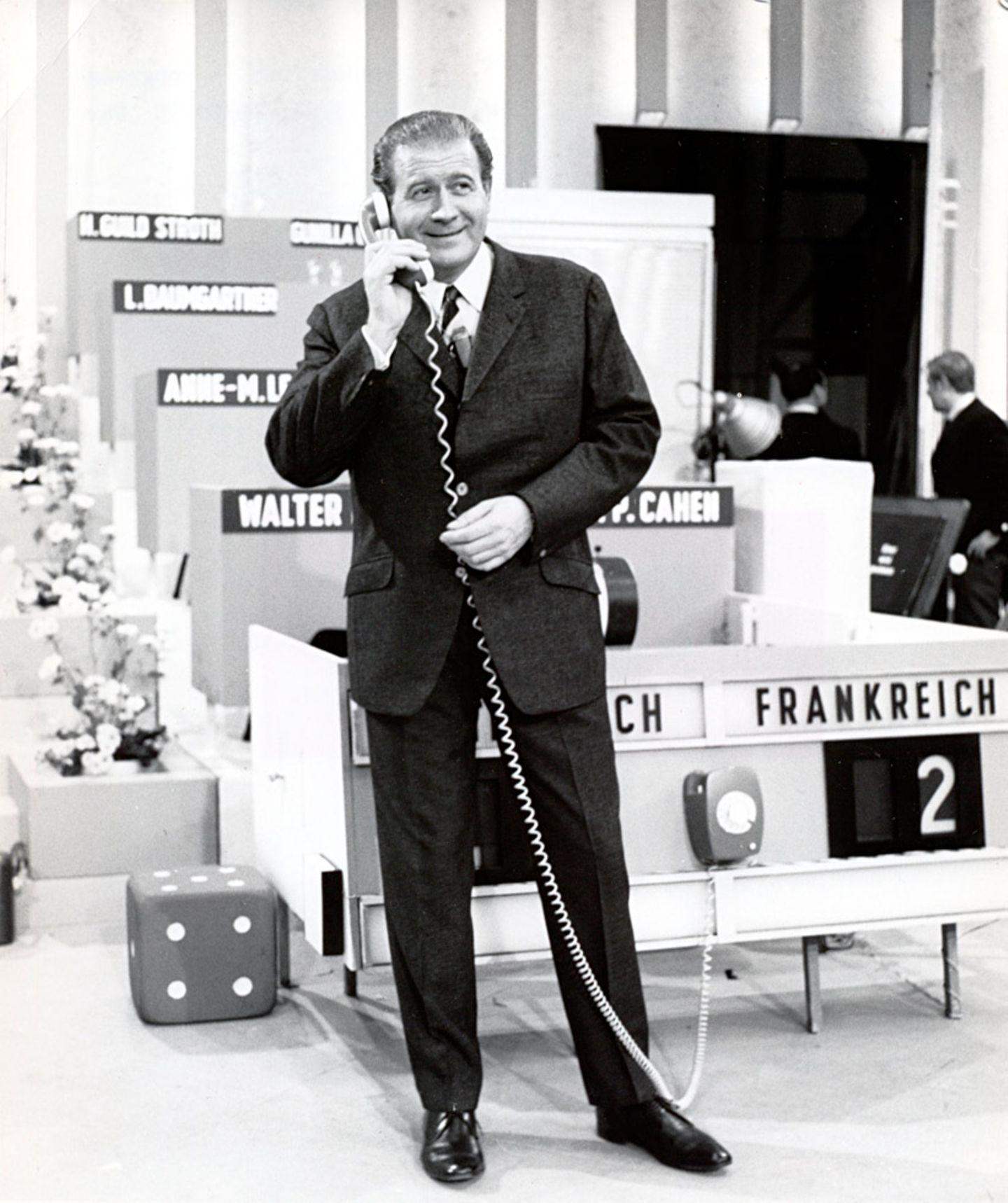 """Hans-Joachim Kulenkampff war der eloquenteste und weltläufigste Moderator, den das deutsche Fernsehen je hatte. 23 Jahre lang, von 1964 bis 1987, moderierte der Charmeur die Samstagabendshow """"Einer wird gewinnen"""". Eine Sendung, die den europäischen Gedanken in die deutschen Wohnzimmer trug: Die Kandidaten kamen aus acht verschiedenen Ländern. Neuauflagen mit Jörg Kachelmann (1998) und Jörg Pilawa (2014) unterstrichen nur, wie sehr wir Kulenkampff vermissen."""