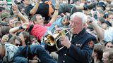 Trompete statt Gitarrenriffs: Die Wacken Firefighters, die Blaskapelle der örtlichen Feuerwehr, spielen zum Festival-Auftakt im Biergarten Volkslieder und Adaptionen bekannter Songs. Im Hintergrund verwandelt sich die tobsüchtige Meute in ein betrunkenes, schunkelndes Menschenmeer.