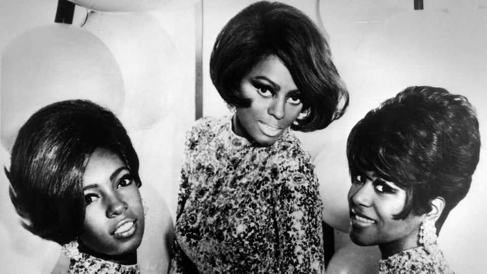 """Im Januar 1959 lieh sich der vormalige Profi-Boxer Berry Gordy 800 Dollar aus, um ein eigenes Plattenlabel zu gründen. Ohne es zu wissen, legte er damit den Grundstein zu einer Erfolgsgeschichte, die weit über die musikalische Bedeutung hinausreicht. Im Amerika der Rassentrennung brachte Motown als eine der ersten Plattenfirmen schwarze Musik zu einem weißen Publikum. Gordys Trick: Er glättete den rauen Soul und legte Wert auf eingängige Melodien. Auf diese Weise schafften es zwischen 1961 und 1971 unfassbare 110 Motown-Songs in die amerikanischen Top Ten.  In seinen Hochzeiten produzierte Motown Hits wie am Fließband - die Arbeitsweise ähnelte derjenigen der großen Autofabriken in Detroit. Feste Komponisten-Teams wie das Trio Holland-Dozier-Holland entwickelten die Songs. Das Studio war bis zu 22 Stunden am Tag geöffnet, und die Hausband The Funk Brothers spielte für alle Künstler des Labels. Der erste Nummer-Eins-Hit hatte Motown 1961 mit """"Please Mr. Postman"""" von den Marvelettes. Ein Song, den auch die Beatles später covern sollten.   Die erfolgreichste Gruppe waren die Supremes um Lead-Sängerin Diana Ross (Mitte), die in den 60er Jahren zwölf Nummer-Eins-Hits hatten, darunter """"Baby Love"""", """"Stop! In the Name of Love"""", """"I Hear a Symphony"""", """"You Can't Hurry Love"""" und """"You Keep Me Hangin' On""""."""