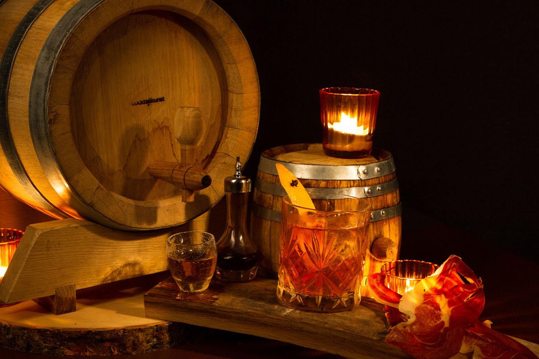 Bacon & Barrel Old Fashioned    Wer schon einmal ein ordentliches Barbecue erlebt hat, der weiß, wie sehr gutes Fleisch und Bourbon harmonieren. Klar, dass dieses klassisch amerikanische Ritual sich auch in einem klassisch amerikanischen Drink einfangen lässt – dem Old Fashioned. Die Fasslagerung sorgt zusätzlich für eine Verschmelzung der Aromen und für ein vielschichtiges Trinkerlebnis.  Zutaten:  700ml Serrano-Schinken-Bourbon Whiskey*  200ml Läuterzucker  15 Dashes Angostura Bitters  Trinkgefäß: Tumbler  Garnitur: Mit Nelken gespickte Orangenzeste  Zubereitung:  Alle Zutaten für ungefähr 4 Wochen im Eichenfass lagern. Zwischenzeitlich den Geschmack prüfen. Pro Glas 90ml abzapfen und im vorgekühlten Tumbler auf Eiswürfeln verrühren.  *280g Serrano-Schinken und 700ml Erdnussöl in einen Vakuumbeutel geben. Verschlossen für 6 Stunden bei 70°C im Wasserbad garen. Geben Sie das so gefertigte Serrano-Öl mit dem Bourbon in ein verschließbares Gefäß und schütteln Sie die Mischung kräftig. Lassen Sie das Gefäß über Nacht stehen, sodass sich die Serranofettinfusion und der Bourbon wieder trennen. Stellen Sie die Infusion danach 2 bis 3 Stunden in den Gefrierschrank – so kann das gefrorene Öl vom noch flüssigen Bourbon getrennt werden. Lassen Sie den Bourbon zusätzlich durch einen Kaffeefilter laufen, um restliche Trübstoffe zu entfernen.