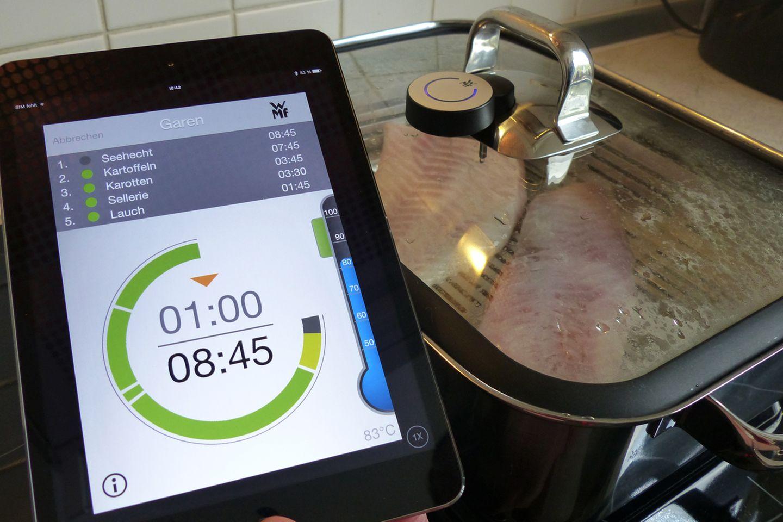 Ab jetzt kocht man im Autopilot: Gibt es etwas zu tun, schlägt das Handy oder Tablet Alarm, etwa wenn die Garzeit einer Zutat erreicht wird oder eine neue Zutat in den Topf gelegt werden muss. Die Zeiten sind dabei so kalkuliert, dass alle Zutaten zum gleichen Zeitpunkt gar sind - Kartoffeln und Hähnchenfleisch müssen also eher eingelegt werden als etwa Spinat. Das Thermometer an der Seite zeigt die Innentemperatur des Kochtopfs, in unserem Fall ist sie 10 bis 15 Grad zu niedrig. Wir drehen den Herd also etwas höher.