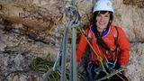 """Kletterin Michelle Knaub  Am Standplatz durch mehrere Haken im Fels gesichert. Das extreme Klettern in den Dolomiten erfordert zur Sicherung auch einen großen Materialeinsatz. Bei einer Tour durch die Nordwand benötigt eine Seilschaft ein gutes Dutzend Express- und Bandschlingen sowie einen Satz Keile und """"Friends"""" - kleine Klemmkeile, die sich in Felsspalten fixieren lassen."""