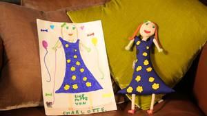 """Charlotte war die schnellste: Die siebenjährige Tochter unseres Kollegen malte ein Mädchen im Blumenkleid mit einem Hund an der Leine und Ballons rundherum. Als sie ihre Puppe überreicht bekam sagt sie: """"Dass die sogar alle Fehler, die ich beim Malen gemacht habe, extra genäht haben! Da sieht ja fast so aus, als wäre die Puppe zuerst dagewesen und ich hätte sie abgemalt!"""""""