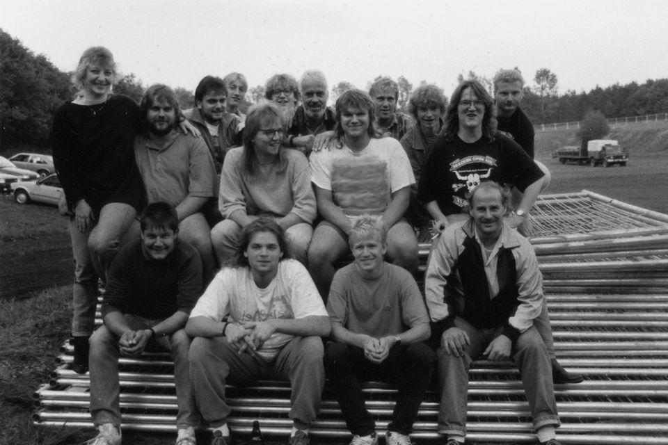 """Alles begann im Jahr 1990, damals kamen 800 Leute nach Wacken. Organisiert wird das Festival seit damals von Thomas Jensen (zweite Reihe, schwarzes T-Shirt, rechts) und Holger Hübner. Alles ging damals noch familiär zu in der Kuhle, so hieß das ursprüngliche Festivalgelände. Jensens Bruder kümmert sich um Getränke und Verpflegung, die Organisatoren selbst zapften Bier und sorgten für die Musik. Jensen spielte in seiner Band """"Skyline"""" Bass, Hübner legte als DJ Rock- und Metal-Platten auf."""