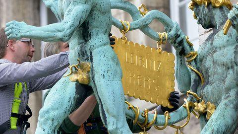 Zwei Mechaniker hängen den goldenen Keks wieder dorthin, wo er hingehört - ans Bahlsen-Firmengebäude in Hannover.