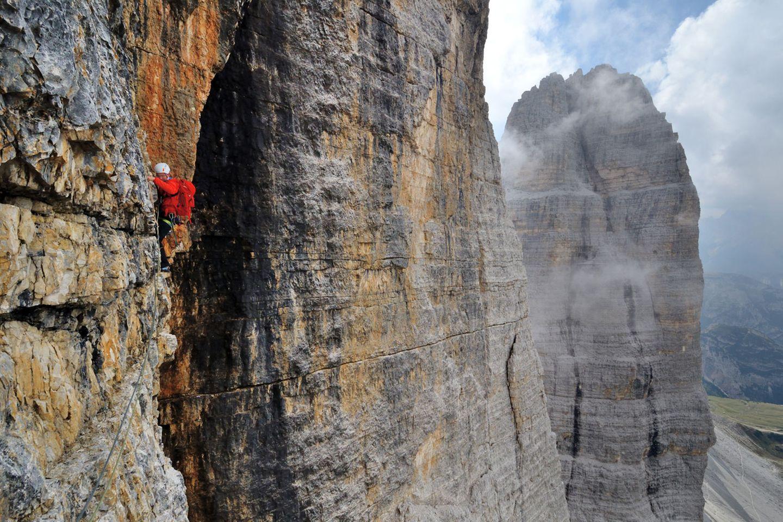 """Große Zinne: Nordwand  Im selben Jahr 1933 wurde von Emilio Comici nicht nur die """"Gelbe Kante"""", sondern auch die Nordwand der Großen Zinne (2998 Meter) erstmals bezwungen. Die """"Comici"""" gehört bis heute zu den ganz großen Klettertouren in den Alpen. Nirgendwo fühlt man sich so verloren wie in diesem vertikalen Ozean aus gelben Fels. Rechts im Bild die Westliche Zinne."""