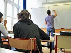 Ein junger Lehrer beschriftet die Tafel. Nachwuchslehrer sind knapp, die Bundesländer werben sich die Kräfte gegenseitig ab