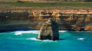 Vom Helikopter aus bietet sich ein grandioser Blick auf einsame Felsriesen vor der buntgestreiften Steilküste im Süden Australiens