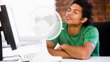 Hitze im Büro: Ein mann sitzt vor einem Ventilator