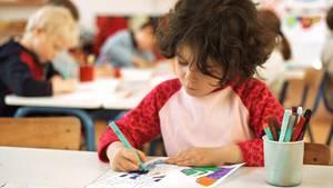 Malendes Schulkind im Klassenraum