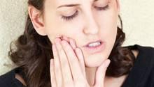 Zahnschmerzen: Eine Frau hält sich die Wange