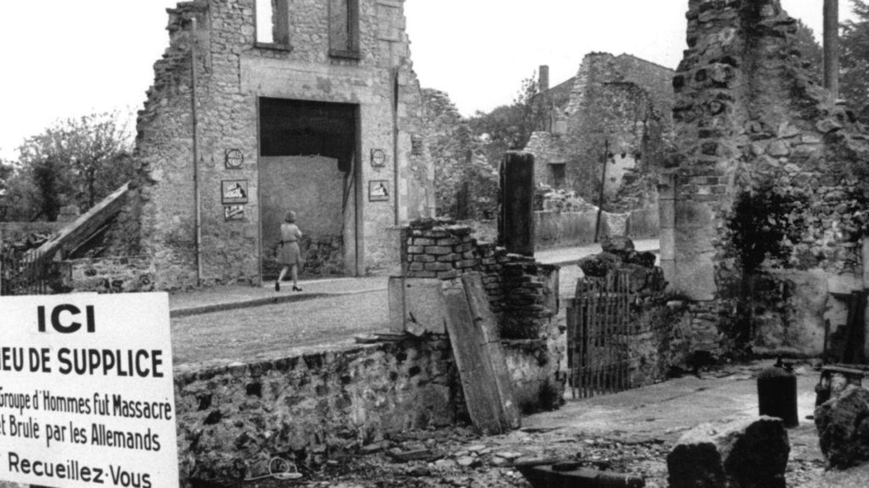 """Blick auf die Ruinen von Oradour-sur-Glane und eine Gedenktafel, deren Text lautet: """"Gedenkstätte: Eine Gruppe von Männern wurde hier von den Deutschen massakriert und verbrannt. Besinnt Euch"""""""
