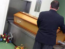 Ein Sarg in einem Krematorium wird in die Verbrennungsanlage geschoben. Die Angeklagten sollen sich in 600 Fällen bereichert haben