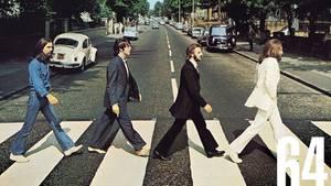 """Die Musikgruppe """"The Beatles"""" läuft über den Zebrastreifen der Abbey Road."""