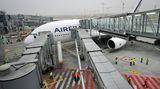 """Applaus bei der Landung  Die Flughafenfeuerwehr begrüßt den Neuankömmling mit Fontänen im Regen, das Bodenpersonal steht Spalier. Durch die drei parallelen Fluggaststeige verläuft das Aussteigen zügig. Flughäfen, auf denen der neue Superjumbo landet, müssen entsprechend umgerüstet und """"A380-fähig"""" sein, um auf zwei Ebenen die Passagiere abfertigen zu können"""
