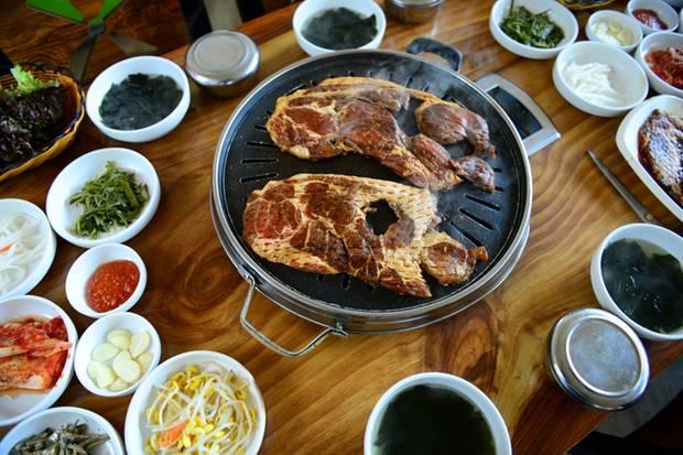 Ein Tischgrill mit vielen Beilagen. Hier handelt es sich nicht um Bulgogi, sondern um ein ganzes Stück Fleisch.