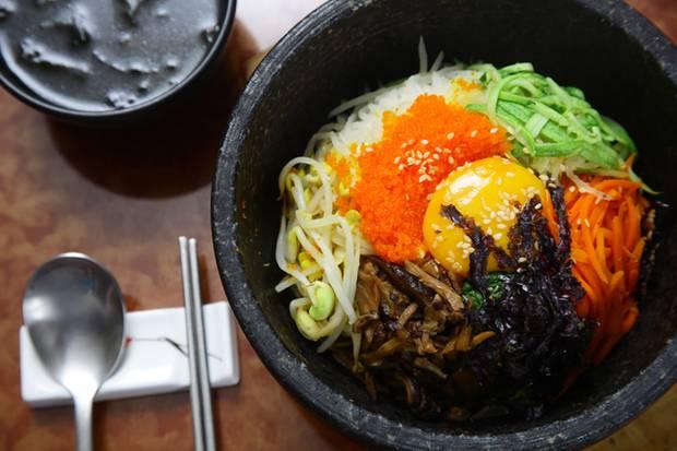 Hier ist eine Variante des Bibimbap zu sehen. Das Dolsot Bibimbap wird im heißen Steintopf serviert. Dadurch wird das Gericht während des Essens weiter erhitzt und gebraten. Das Ei wird oft roh darüber geschlagen.