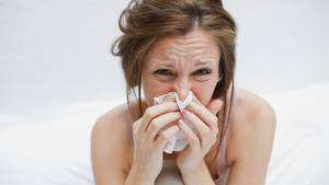 Frau im Bett putzt sich die Nase