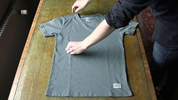 Person faltet T-Shirt