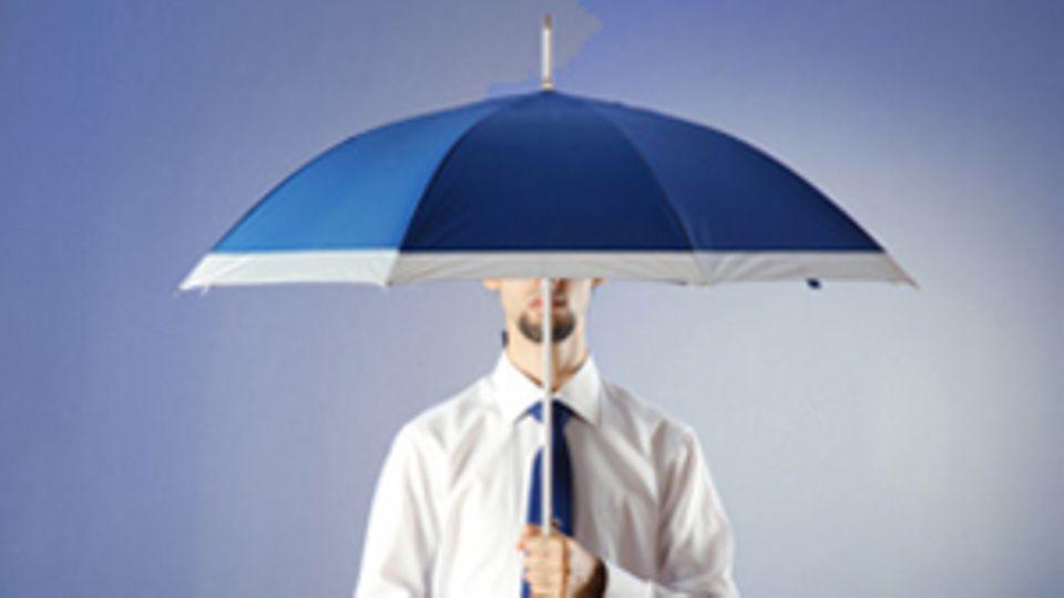 EIn Mann steht unter einem Regenschirm.
