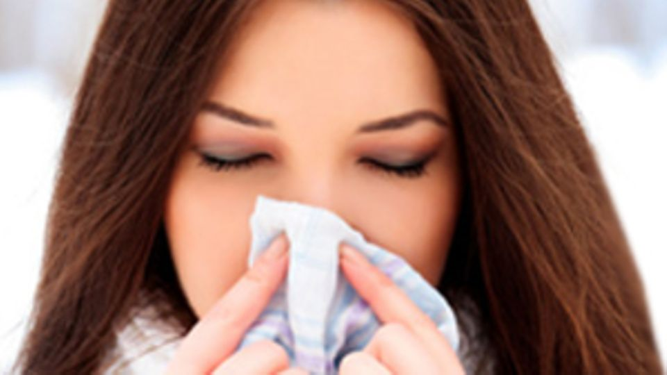 Eine Frau hält sich ein Taschentuch vor die Nase.