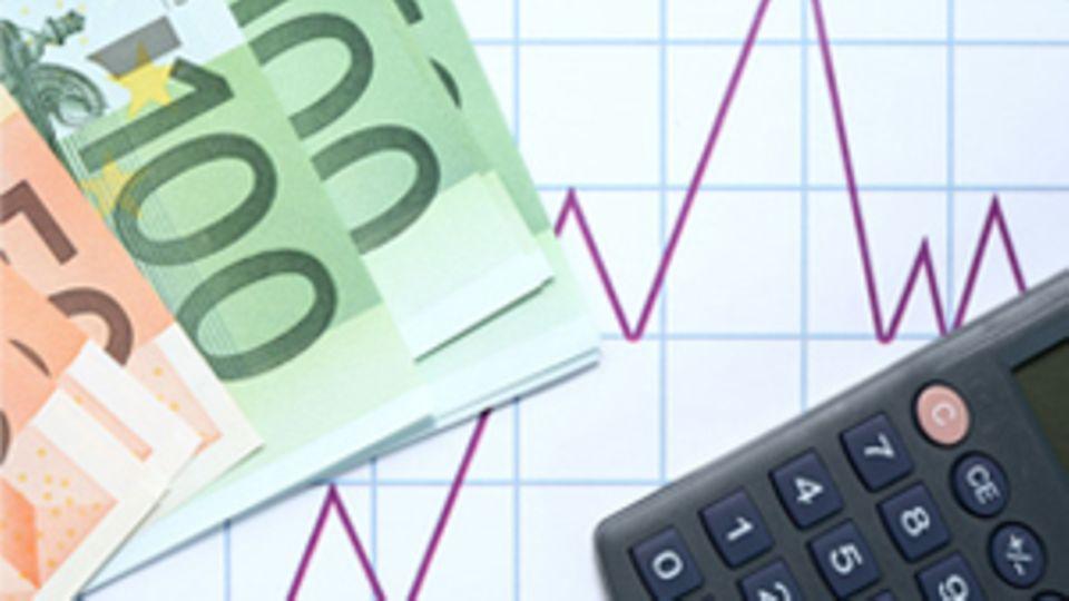 Geldscheine liegen neben einem Taschenrechner auf einer, auf ein Blatt Papier, gezeicheneten Graphik.