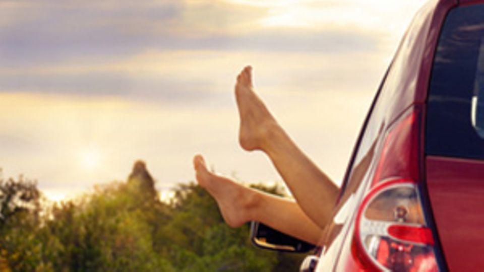 Nackte Füße werden aus dem offenen Fenster eines Autos gestreckt.