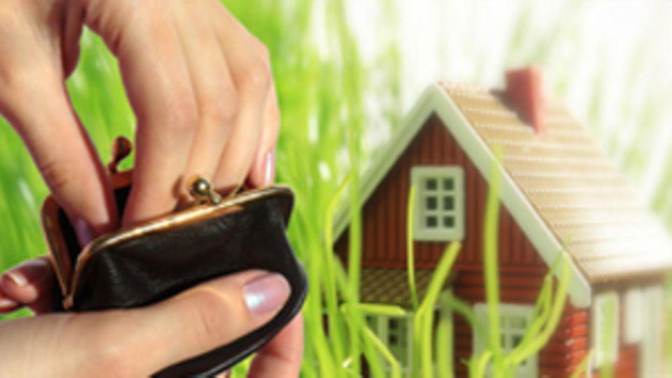 Eine Hand greift in ein kleines Portemonnaie. Im Hintergrund steht ein Haus.