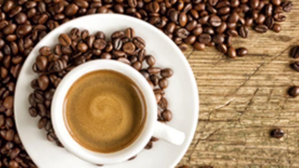 Eine Kaffeetasse um die Kaffeebohnen verstreut sind.