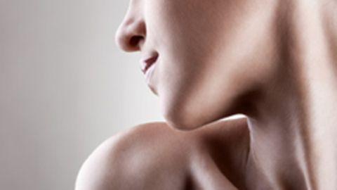 Bildasuchnitt einer Frau, die sich über die Schulter schaut. Sichtbar sind der untere Teil ihres Gesichts und ihre Schulter.