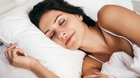 Eine Frau liegt schlafend im Bett.